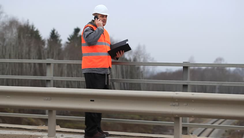 Engineer with a cell phone and a folder on the bridge