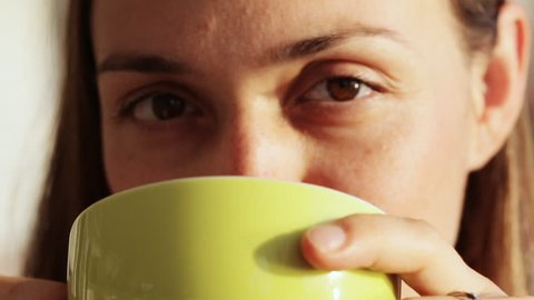 Young pretty woman sits in cafe with cup of tea or coffee and gulping. Close-up of hands with cup and then face of drinking woman in warm sunrise light. Girl looking at camera and smiling.