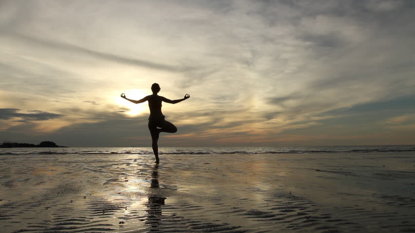 Young woman practicing yoga on the beach at sunset (HD)