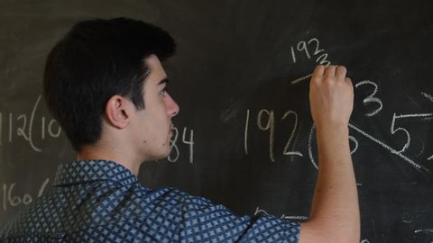 Male teenager trying to solve math equation at high school blackboard