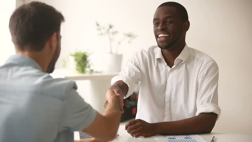 Happy satisfied diverse businessmen making commitment handshaking after successful negotiations, african black entrepreneur shaking hand of new caucasian white partner closing good business deal | Shutterstock HD Video #30602845