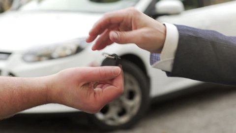 A car being bought / sold. A man buying / selling  a car to another man and handing over the key.