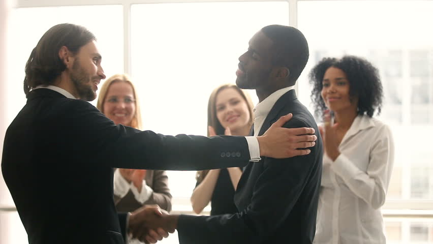 Boss promoting rewarding african american male worker, appreciating for good job, businessmen wearing suit congratulating shaking hands with applauding staff standing in office, employee recognition | Shutterstock HD Video #30610945
