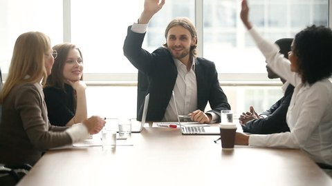 Happy motivated successful team put join hands up together, five partners giving high-five sitting at conference table in office, expressing unity in business, promising help and support in teamwork