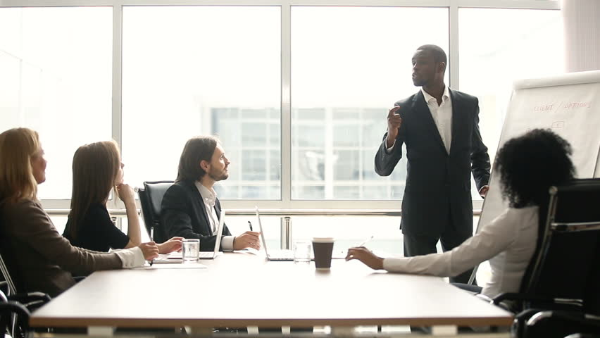 African american coach gives corporate presentation for businesspeople in office, dark skinned businessman presents new business plan on whiteboard, speaking to clients listening speaker at meeting | Shutterstock HD Video #30610993