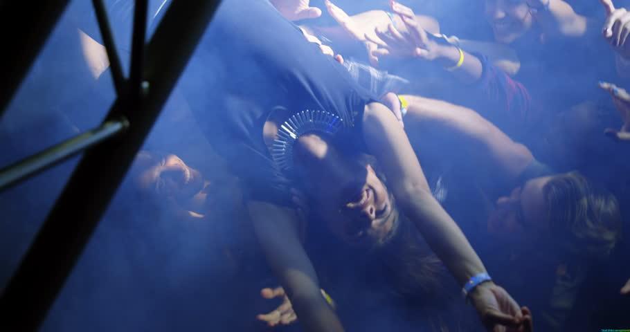 Crowd surfing at a concert in nightclub 4k
