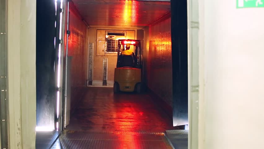 Pallet lift driving with milk package. Forklift move in dairy factory warehouse. Forklift carries packages of milk bottles. Pallet transport
