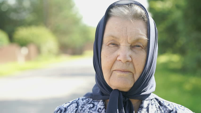 Portrait of smiling mature old woman with gray hair in a black handkerchief on the background of road in summer. Close-up