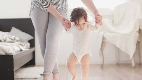 Baby taking first steps with mother help