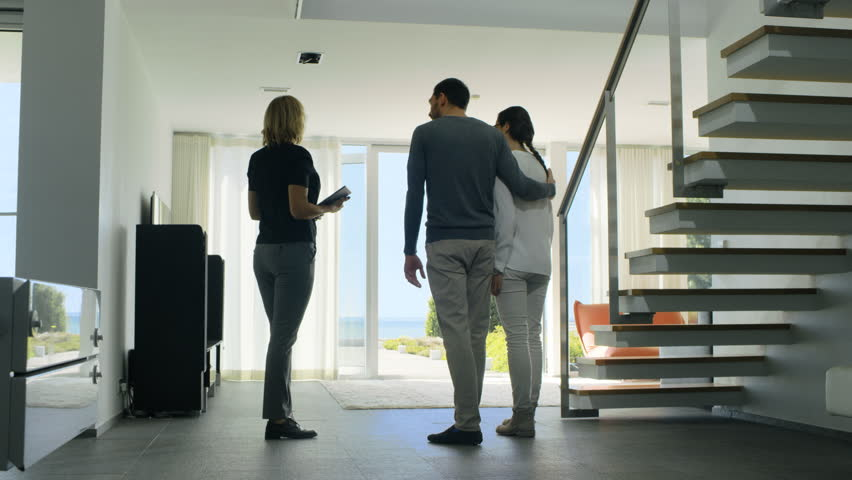 Professional Real Estate Agent Shows Stylish Modern House to a Beautiful Young Couple Who are in the Market for Purchasing/ Renting New Home. House Has Floor to Ceiling Windows and Seaside View.4K UHD