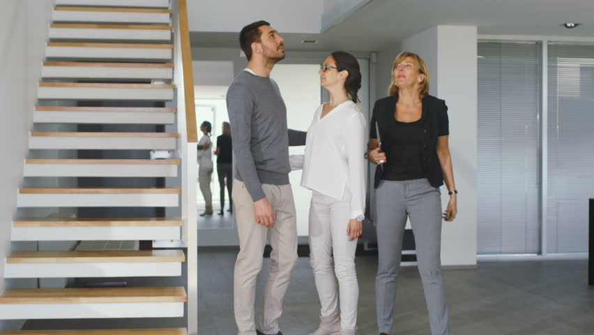 Professional Real Estate Agent Shows Stylish Modern House to a Beautiful Young Couple Who are in the Market for Purchasing/ Renting New Home. House is Modern, Stylish and Bright. 4K UHD. | Shutterstock HD Video #30700855
