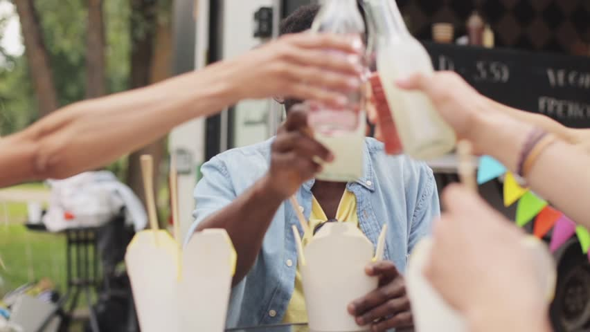 Leisure, celebration and people concept - friends clinking bottles of non-alcoholic drinks and eating wok at food truck | Shutterstock HD Video #30711835