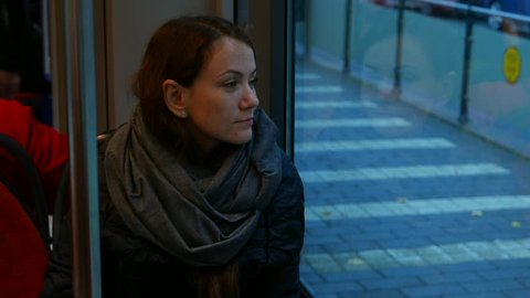 Young woman sit in tram lean to window, look to dusk street, dreamy eyes and faint smile on her face. Vehicle stay on stop, empty pavement with white lines seen outside. Girl face reflection in glass
