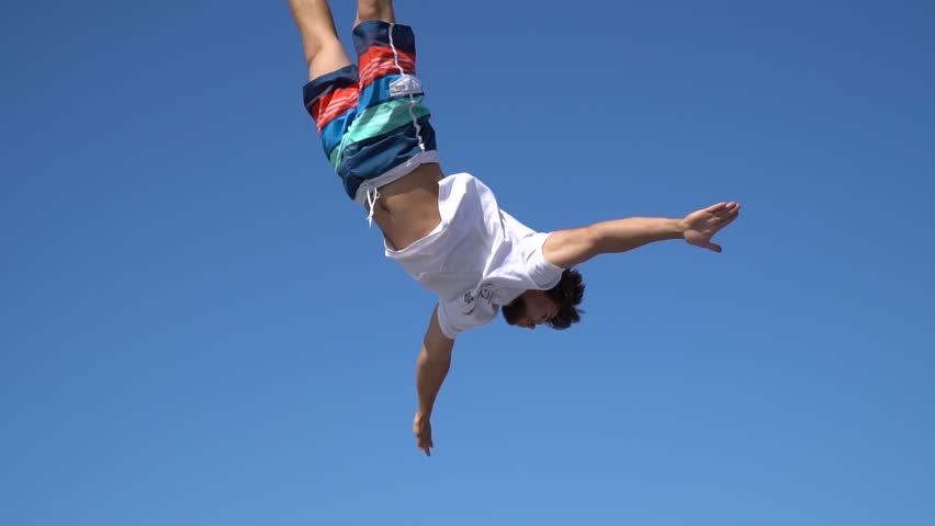 A man against the blue sky bounces into the air, slow motion #30825925