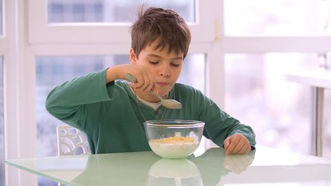 Boy child eating cereal cornflakes from bowl HD slow-motion video. Kid morning breakfast of corn flakes and milk.