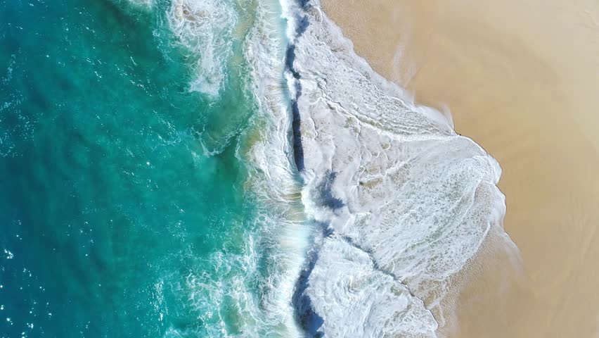 Aerial view waves break on white sand beach at sunset. Sea waves on the beautiful beach aerial view drone 4k shot.