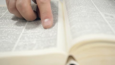 Man finds the information in the reference book. Close up shot of man's hands turning the pages of a reference book.
