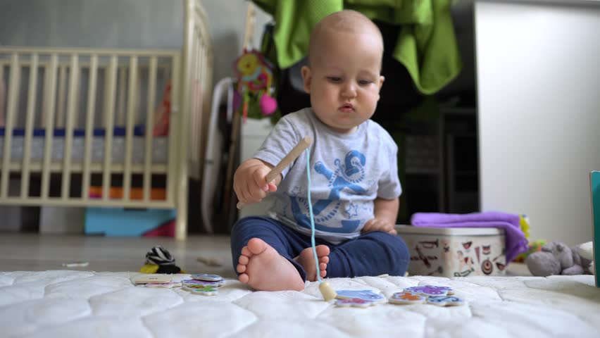 ?ute baby boy plays with magnet fishing rod and is happy to catch a toy fish