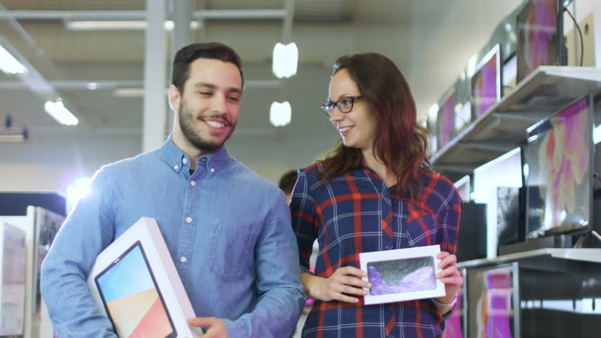 Happy Couple Walking In the Electronics Store, They've Purchased Latest Model of the Tablet Computer for Him and New Smartphone for Her. Shopping Center is Big, Bright and Full of Newest Electronics.  | Shutterstock HD Video #30883945