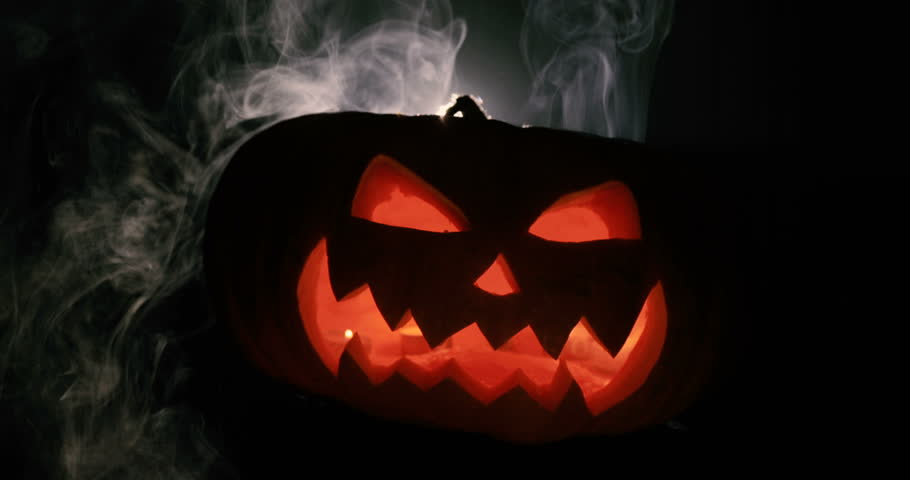 Scary carved halloween pumpkin in hot burning hell fire flames. The big helloween pumpkin has a mad face with glowing eyes and also a smoke in its mouth and teeth. | Shutterstock HD Video #30886795