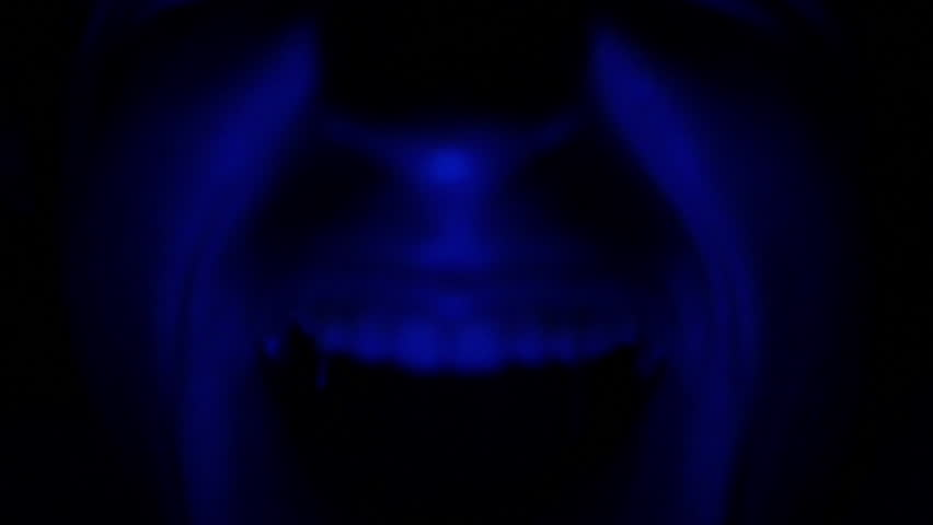 Distorted Screaming Horror Face Illuminated with Blue Light in Darkness