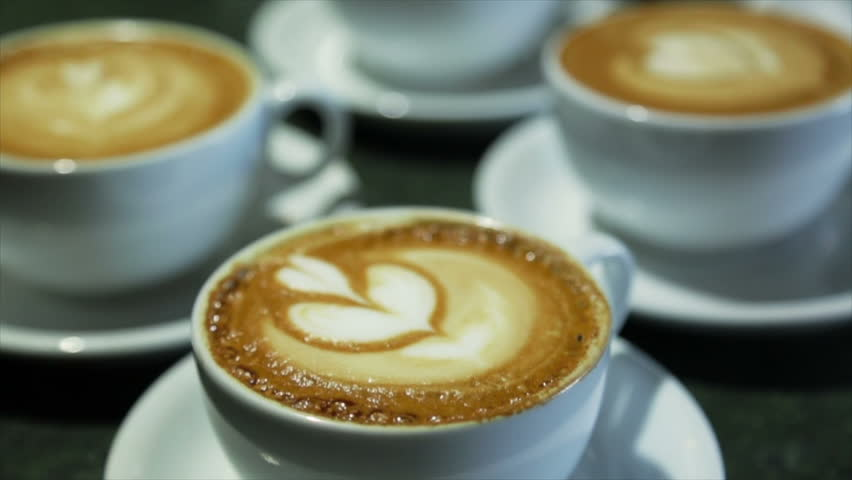 White and small cups served with art latte on the table of a bar