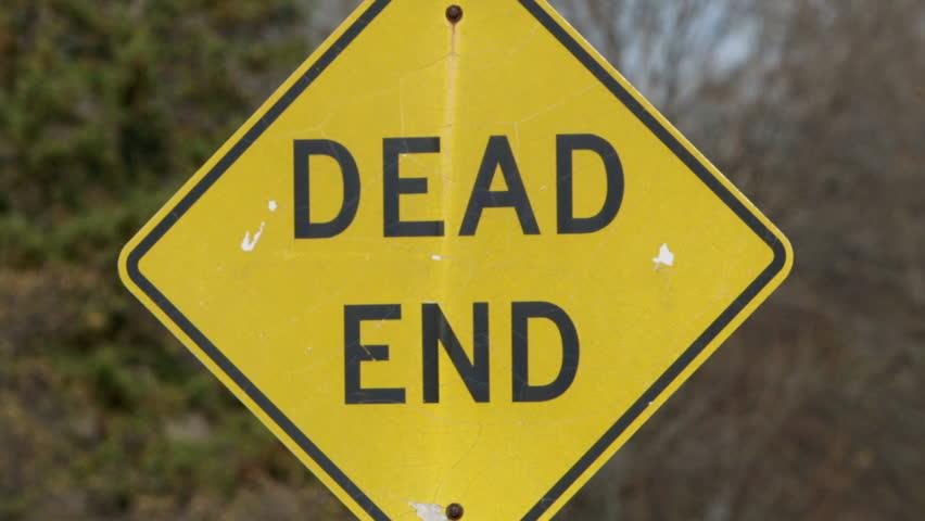 "Tilt up and hold on a ""Dead End"" sign on a neighborhood street."