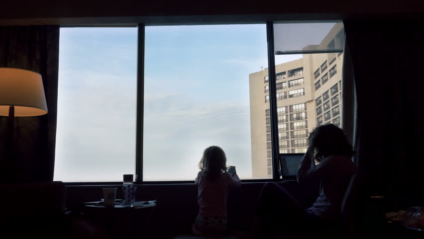 Silhouettes of mother and daughter in front of window. Three quarter length.