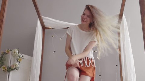 Happy young blonde female whith pretty long hair in pajama jumping and dancing on bed in morning and smiling. Woman in cheerful mood. Slow mo .