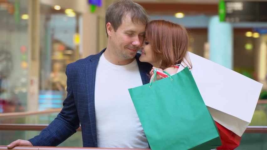 Young couple talk and have fun with packages of purchases in shopping center. Couple smiles with multi-colored packages after Christmas shopping