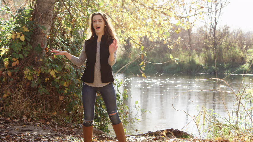 Young woman dancing and laughing in front of a lake.