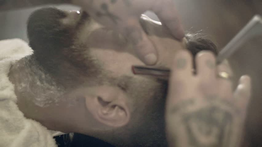 Beard cut with straight razor shave. Close up of shaving beard in barber shop. Male beard style. Barber shaving hipster man face | Shutterstock HD Video #30988165