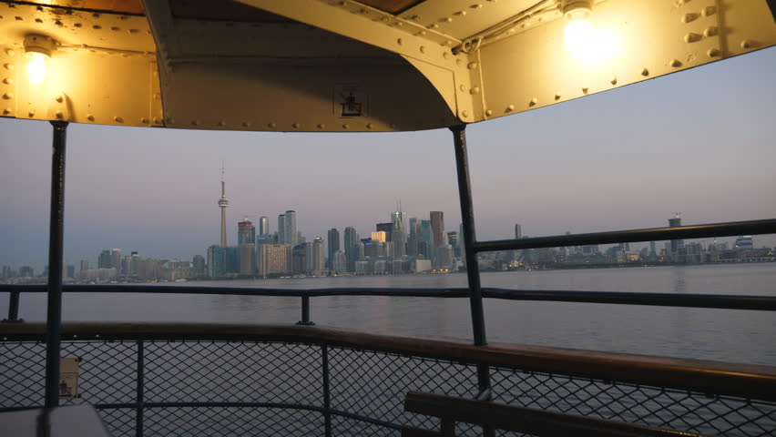 Dawn view of Toronto skyline as ferry Sam McBride pulls into Ward's island. Summer. Seagulls fly by.