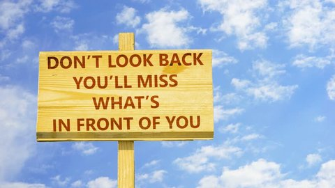 Don't look back. You will miss what is in front of you. Words on a wooden sign against time lapse clouds in the blue sky.