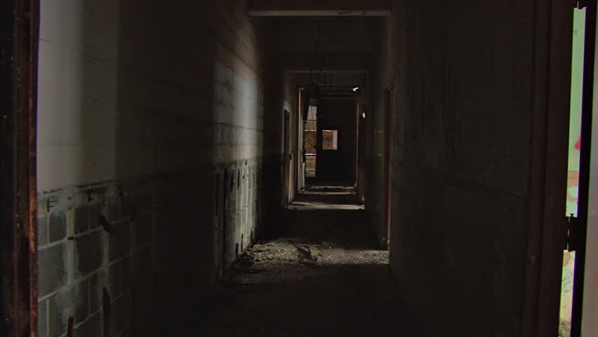 A dark hallway of nasty ruin and decay in a wretched, decrepit abandoned building. Glidecam shot.