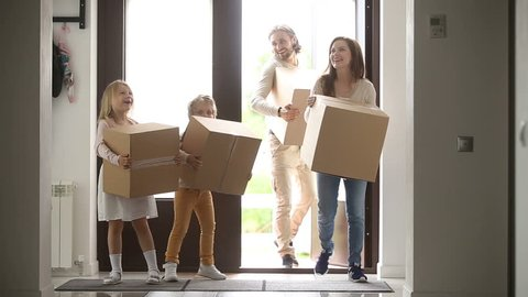 Happy family with kids holding boxes entering new modern house, excited couple and children relocating carrying belongings, opening entrance door looking around while moving in own bought rented home