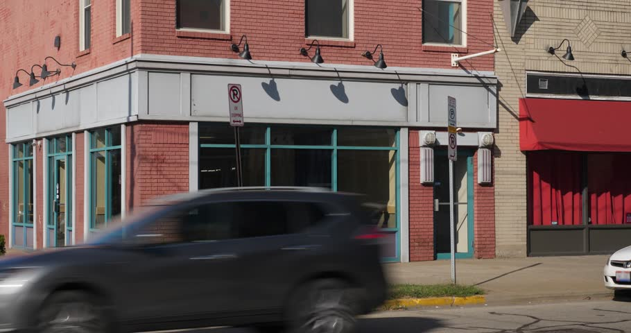 A generic, unbranded corner storefront with large windows in a large city's business district as traffic passes by.   | Shutterstock HD Video #31073035