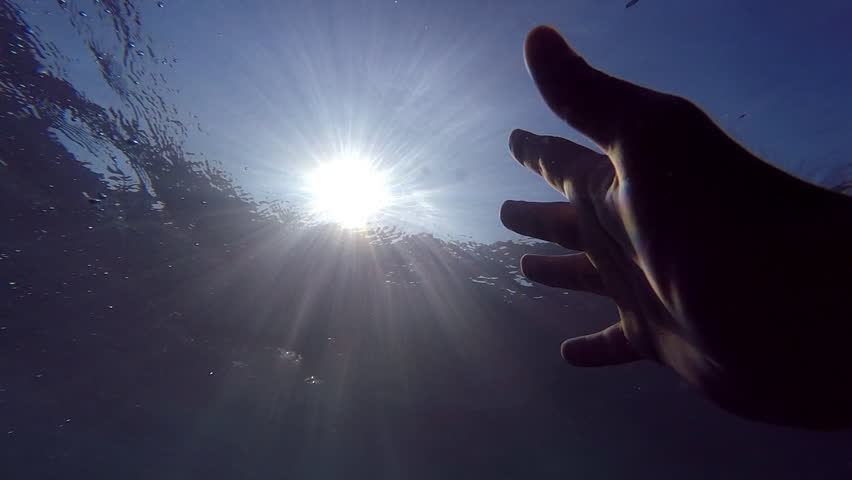 Male hand stretches from under the water to sunrays. Arm asking for help and trying to reach to the sun. Point of view of man drowning in the sea or ocean and floating to the surface. Slow motion POV