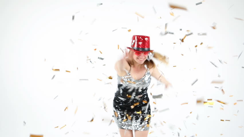 Fun dancing young woman in red bright hat and shiny black dress with sequins. flying confetti in the air. atmosphere of celebration party and fun. White background. Video footage.