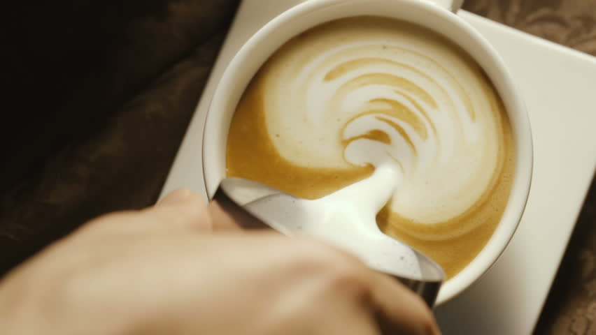 Pours milk into a coffee cup in a cafe