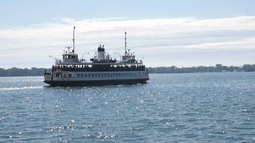 Slow motion view of public ferry, Sam McBridge leaving Toronto for the Toronto islands. Sparkling water. Summer in Toronto.