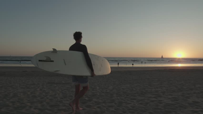 Surfer walking towards the ocean in Venice Beach, California / Surfing, slow-motion, breathtaking sunset view