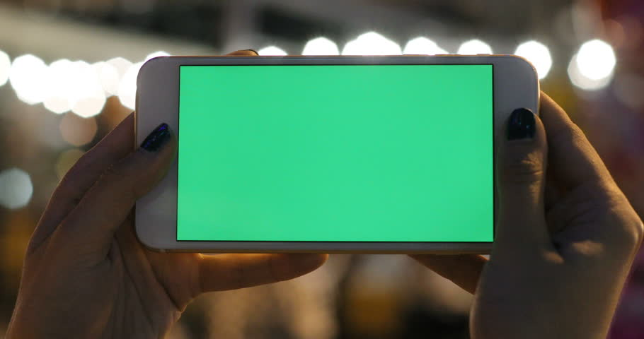 Woman hands horizontal holding smart phone mobile green screen chromakey blurred background unficused light beams shimmer digital device closeup display night city street modern tech taking picture