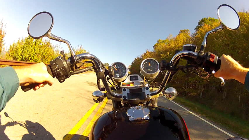 A wide angle shot of the point of view of someone riding a motorcycle on a curvy
