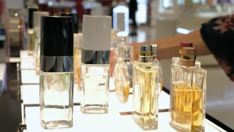 Female Hand Choosing Luxury Parfume In Cosmetic Store. Closeup.