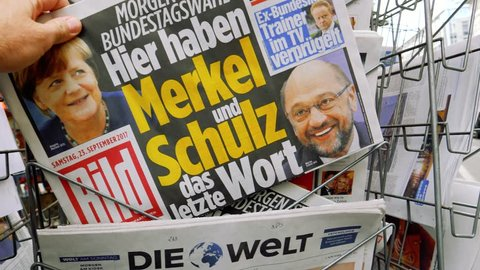 PARIS, FRANCE - SEP 23, 2017: Man buying latest newspaper Die Bild with with portrait of Angela Merkel And Martin Schulz before the election in Chancellor of Germany, the head federal government