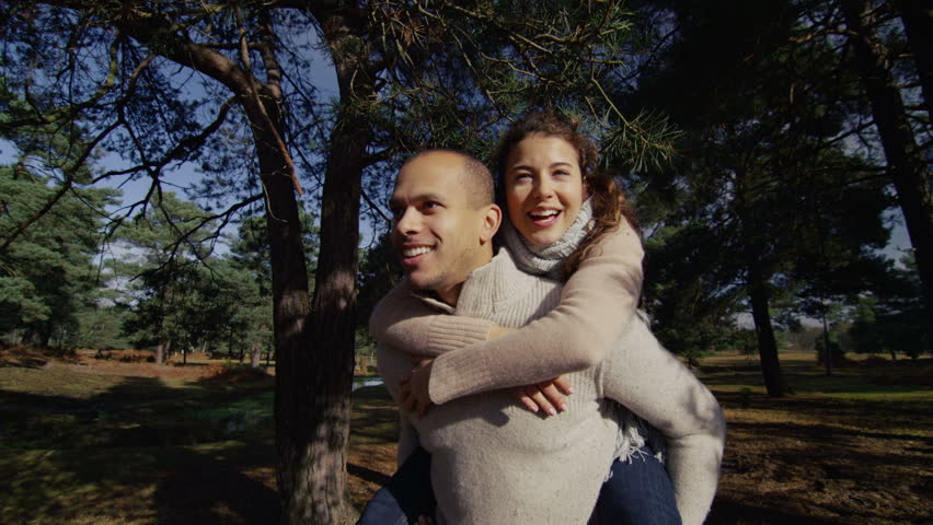 A couple are walking through the trees in a forest and the man is carrying the woman on his back, they are smiling and laughing. In slow motion.