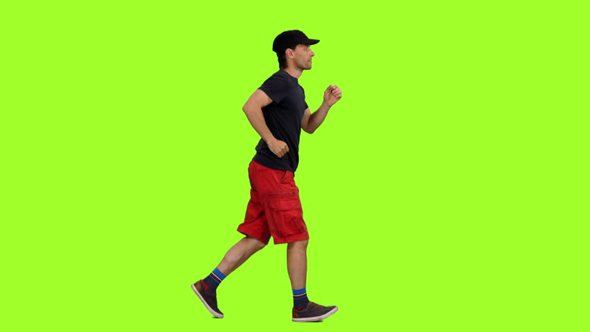 Side view of male in red shorts and black t shirt jogging on green screen background, Chroma key, 4k footage