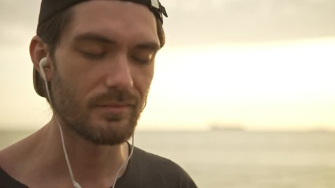 caucasian happy bearded guy with cap on backward listening music using headphones with closen eyes on sunrise over sea background in slowmotion closeup