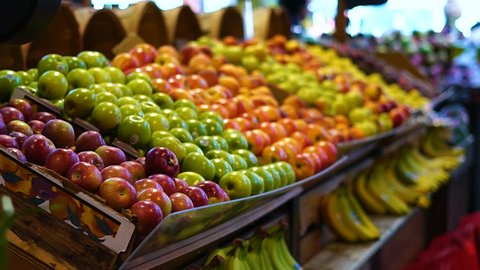 Smooth & steady shot of fruits in a farmer's market (apples, bananas, apricots etc.)